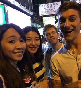Four people smiling on Hong Kong street. One is holding a Chinese beer.