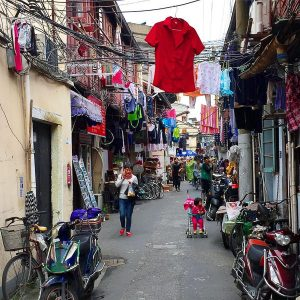 Chinese alleyway in Old Shanghai. A woman talks on her phone as she passes under a maze of hanging clothes. A baby is in a stroller to her left, next to moto delivery bikes.