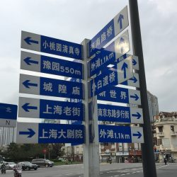 Blue and white street sign displaying walking distances to destinations on the corner of a Shanghai street.