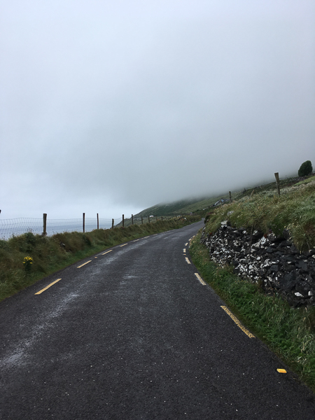 A winding road sits atop a cliff and disappears in the fog in Ireland. I quit my job and disappeared into the fog.