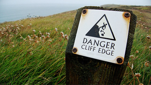 A sign that says Danger Cliff Edge appears on a grassy hill overlooking the sea. The fear of failing can often lead you to not making beneficial changes, like quitting a job you don't like.