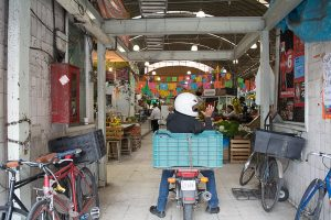 A delivery man takes off one glove as he sits atop his motor bike inside Mercado Medellin in Mexico City.
