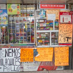 Store front covered in bright colored advertisements under Chapultepec bridge Mexico City