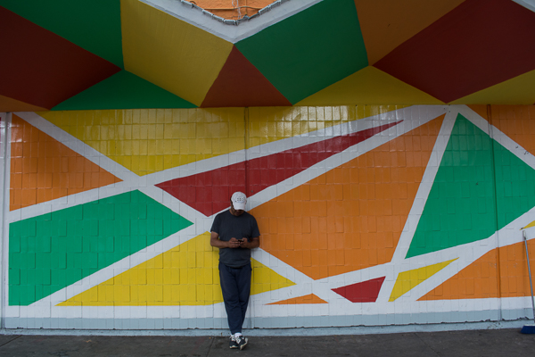Man leaning on multi-colored wall outside of Mercado Medellin in Mexico City. Markets provide an easy way to reduce your cost of living by buying local food.