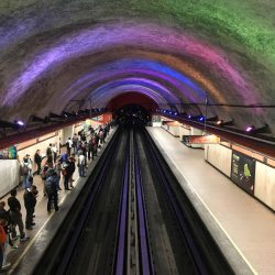 Multi-colored lights change change and create a rainbow atop the tunnel wall inside the Barranca del Muerto station in the Mexico City Metro.