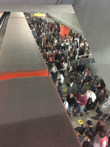Snaking lines of people waiting to board an orange line train on the Mexico City Metro.