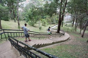 A boy slides down the railing of a steep set of stairs at Cerro Nutibara in Medellin, Colombia.