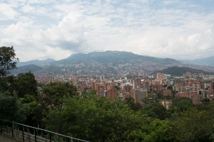 A view of the surrounding valley from one side of Cerro Nutibara in Medellin, Colombia. The trees in the foreground and mountains in the background provide a nice frame to the orange high-rise apartments, centered in the distance.