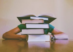 Stack of books in front of a student who has his head down. Information overload can often lead to not taking action.