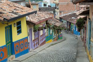 A view from the top of a cobblestone street in Guatapé. Colorful buildings dot the street along the way down.
