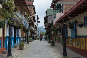 A street leading into Guatapé. Pictured with colorful houses and a motorcycle coming down the cobblestone street.