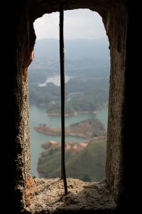 View from inside El Mirador, which leads up to the upper loookout spot in A view of the surrounding lakes an roads below La Piedra del Peñón in Guatapé, Colombia. The small cutout window is in focus here, with the lakes below blurred in the background.
