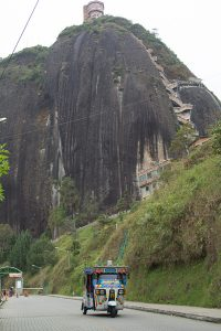 Looking up the road leading to the base of La Piedra del Peñón in Guatapé, Colombia. A tuk-tuk comes down the hill and the set of more than 650 stairs is in view in the background.