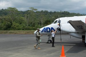 A pilot reverse the propeller after a flight lands at José Celestino Mutis Airport. A uniformed Colombian military man approaches.