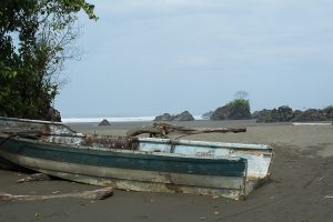 An old wooden rowboat sits on La Playa Almejal in El Valle, Bahia Solano.