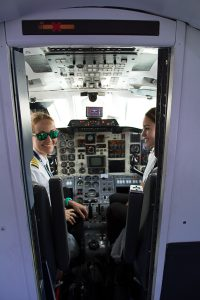 Two pilots smile while in the cockpit of a small prop plane at José Celestino Mutis Airport.