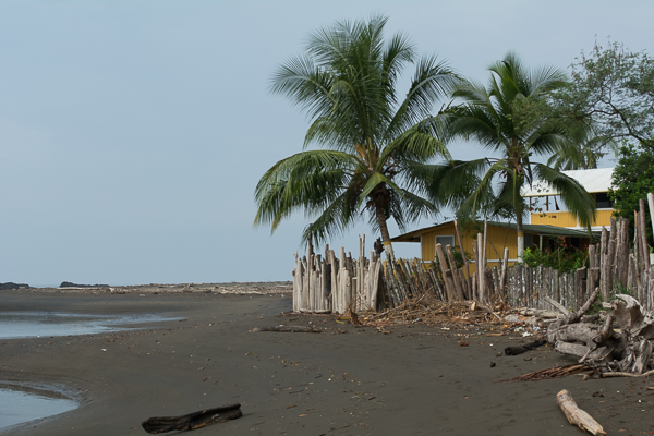 A yellow hostel is pictured on the black shore of Playa Amejal in El Valle, Bahía Solano.