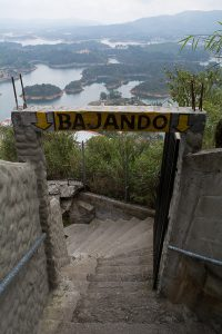 """Stairs leading down La Piedra with a sign above displaying the Spanish verb for going down, """"Bajando."""""""