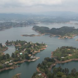 View from the lookout at La Piedra del Peñón in Guatapé, Colombia. The surrounding lakes below are dotted with houses.