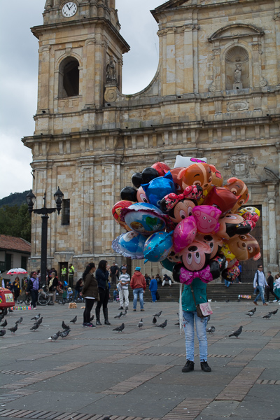 Woman selling balloons in Plaza de Bolivar with Catedral Primada de Bogotá in background