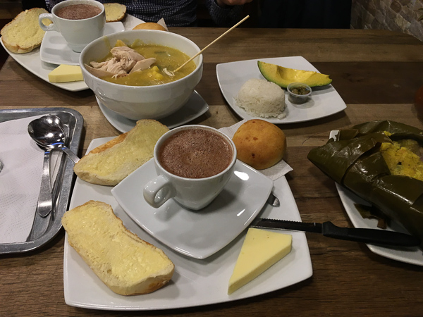 Hot chocolate with cheese plate with bread and ajiaco soup in background