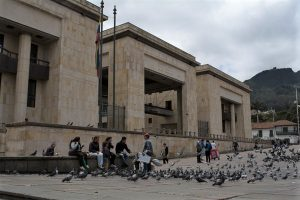 The Palace of Justice is pictured in front of a crowd of people and pigeons in Bolivar Square in Bogota Colombia